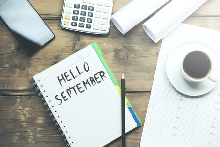 hello september text on paper with stationary
