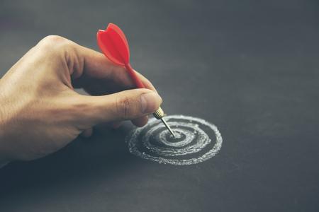 hand neem een pijl in het midden van het schetsen van dartbord