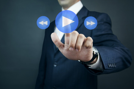 Businessman pressing play button to start or initiate projects