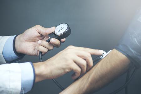 Abgeschnittenes Bild eines männlichen Arztes, der den Blutdruck des Patienten am Tisch überprüft Standard-Bild