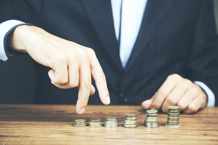 picture of man putting stack of coins into one row Banque d'images