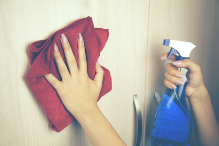 Woman during cleaning white bookstand at home