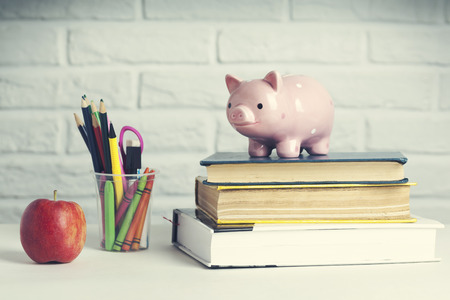 apple and a piggy bank on top of books
