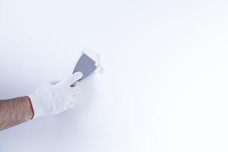 Mature man using scraper to scrape off old wallpaper