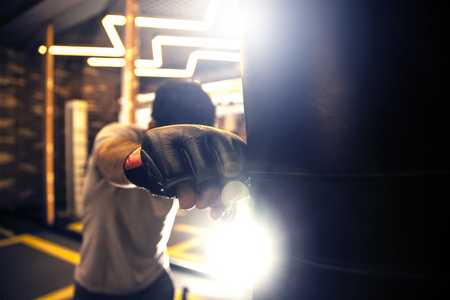 Hand of boxer and punching bag over  background