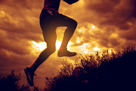 Athletic young man is running in the nature during golden sunset.