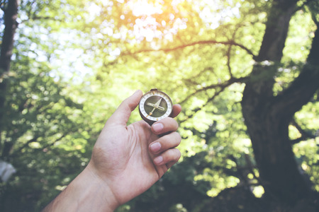 young man hand compass on tree background