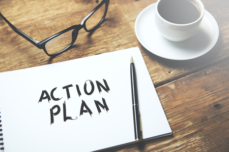 action plan text on notepad with coffee on table