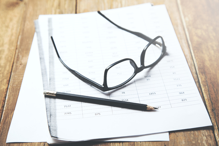 eyeglasses and pencil on document on table 免版税图像