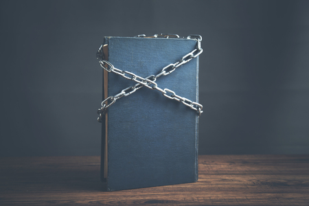 book chained with lock on wooden table