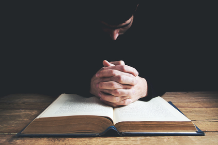 man hands praying with a bible in a dark over wooden table. Imagens