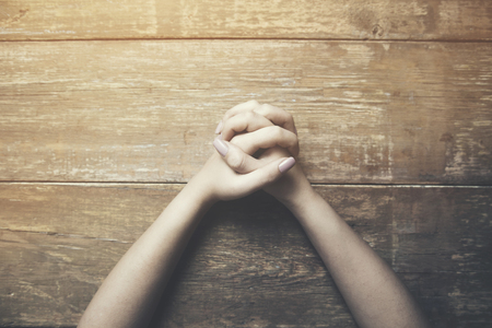 Hands of praying young woman on a wooden desk background.