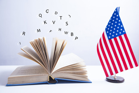 Composition of American flag and  book on white background