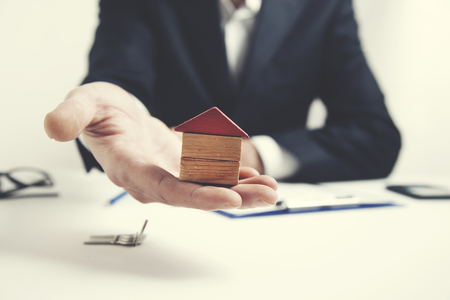 man hand house model on table background