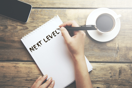 woman written text next level on notepad
