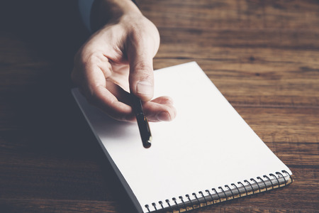 Man hand pen with notepad on table Stock Photo