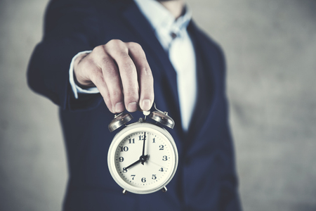 young business man holding clock in hands
