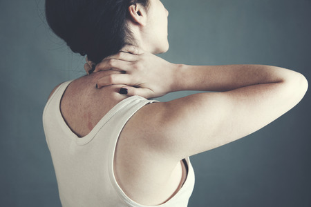 Female placing hands on her neck suffering from pain Stock Photo