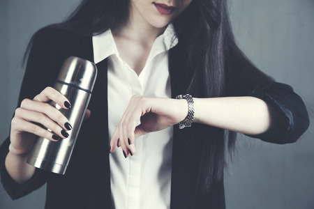 woman hand holding a flask and looking at watch on dark background