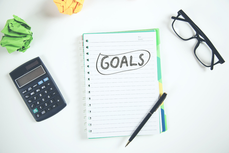 goals text on notepad with stationary on table Imagens