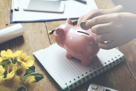woman hand piggy bank and coin on desk