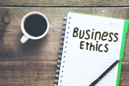 business ethics text on notepad with coffee on table Imagens