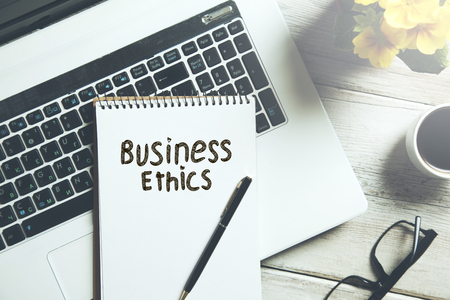 business ethics text on notepad on keyboard