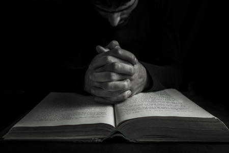 Hands of a human in prayer on a Holy Bible Imagens