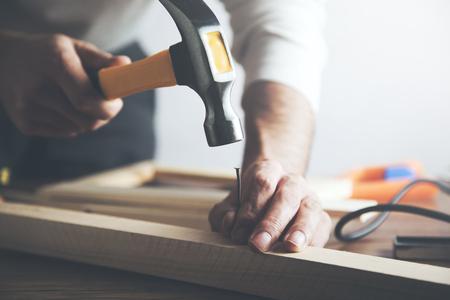 builder holding hummer and scored nail on desk