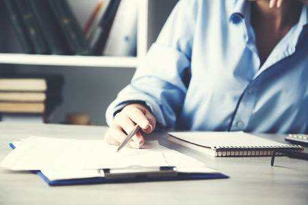 woman hand writing or signing in a document on a desk Imagens