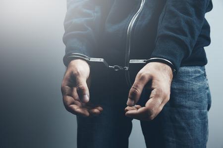 Man hands with handcuffs on the dark background