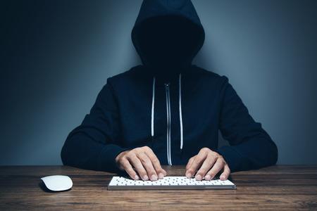 Hacker hand in glove working on laptop Imagens