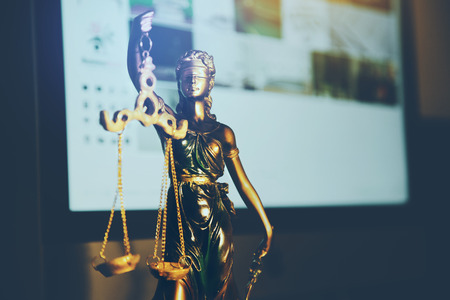 Statue of justice and computer on desk