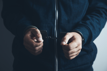 Man hands with handcuffs on white  wall background