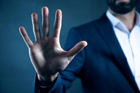 man hand doing stop sign on dark background Banco de Imagens