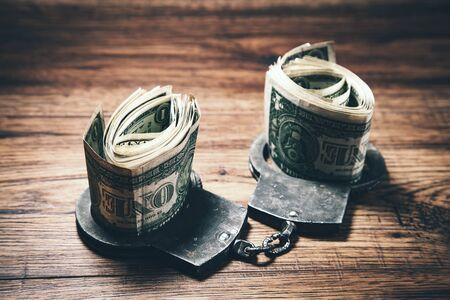 Handcuffs with money on the wooden  table