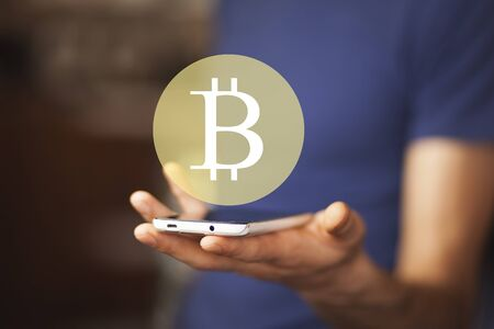 Business man using a smartphone with a Bitcoin