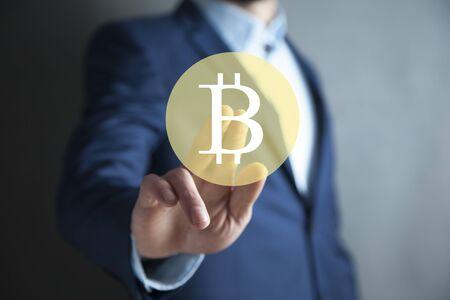 Business man touching  Bitcoin sign in screen
