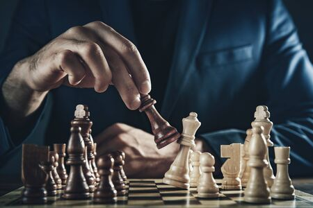 businessman playing a game of chess  on the dark background