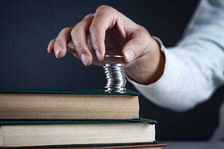 man hand coins on book on dark background