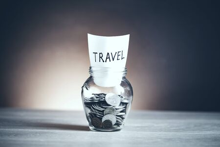 Travel word with coin in glass jar