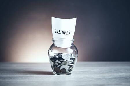 business word with coins in glass jar