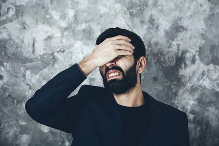 man hand on eye on gray background