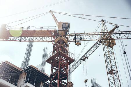 Tower Crane lifting heavy load under sky Stock fotó