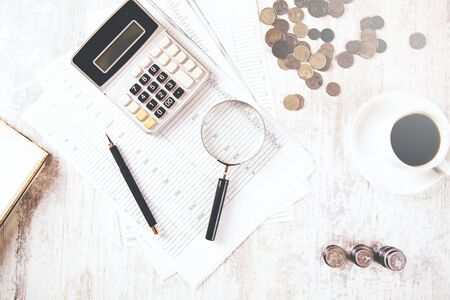 calculator and coins with coffee on document