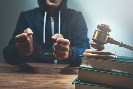 man hand handcuffs and judge on book on table