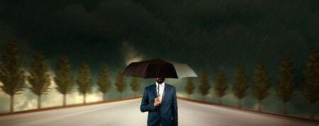 man hand black umbrella in rain Stock Photo