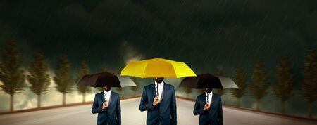 people hands yellow with  black umbrella in rain Stock Photo