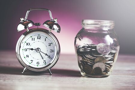clock with coins on jar on table Stok Fotoğraf
