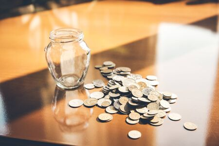 coins on table with jar